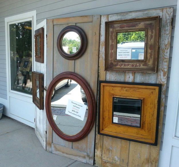 Old door panels make a fabulous backdrop to display these funky framed mirrors - Outside display at The Village Framers in Yarmouth, Maine